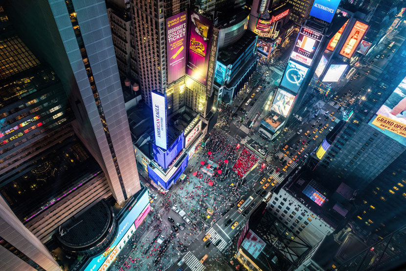 Times Square from above in New York City with tall buildings and skyscrapers at night