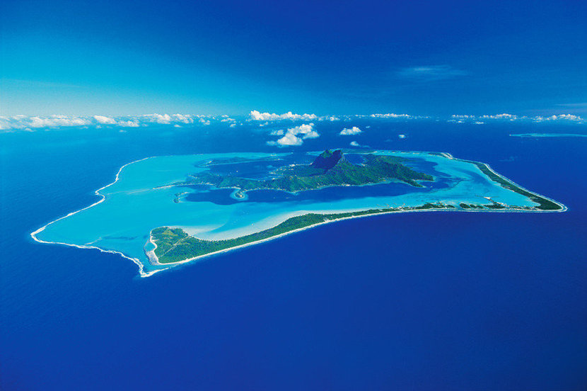 aerial view of bora boar including the bright blue waters and the rings of rich emerald lands of Bora Bora