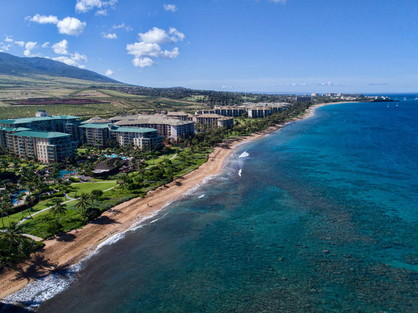 aerial view of kaanapali beach with its white sandy beaches lined by palm trees and rows of resorts surrounded by crystal clear blue water