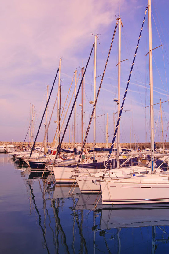 sailboats are anchored at a port as the sun goes down