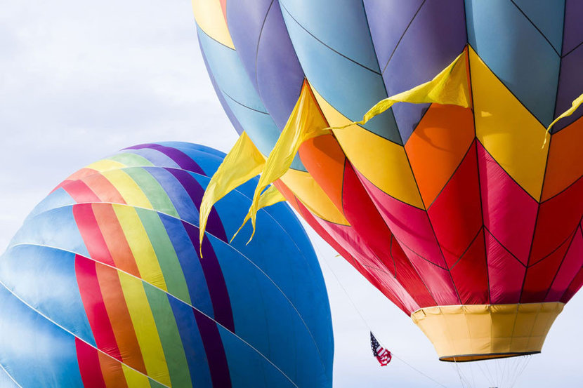 two rainbow colored hot air balloons on display outdoors