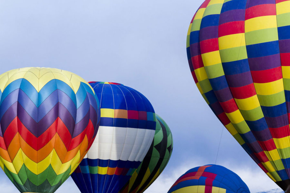 a vibrant image of five rainbow colored hot air balloons on display outdoors