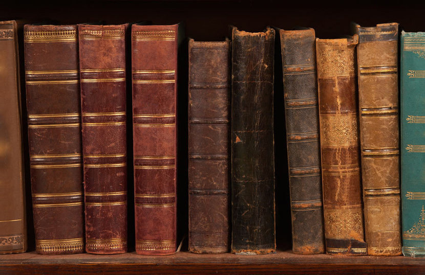 Collection of antique books on a bookshelf wallpaper