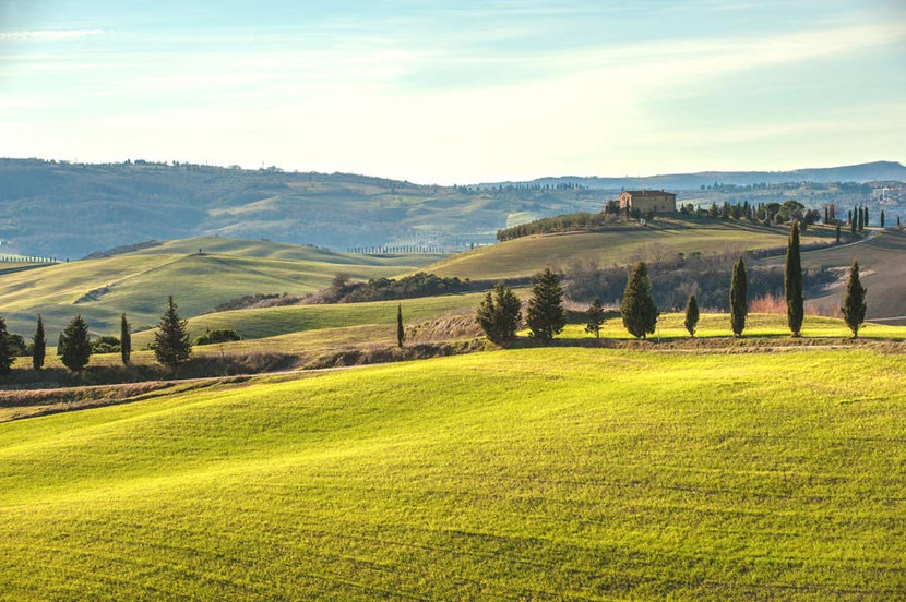 Tuscan landscape with cypresses, wavy fields and a house in the distance
