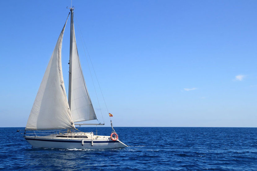 white sailboat rides the waves of the Mediterranean sea on a clear and sunny day.