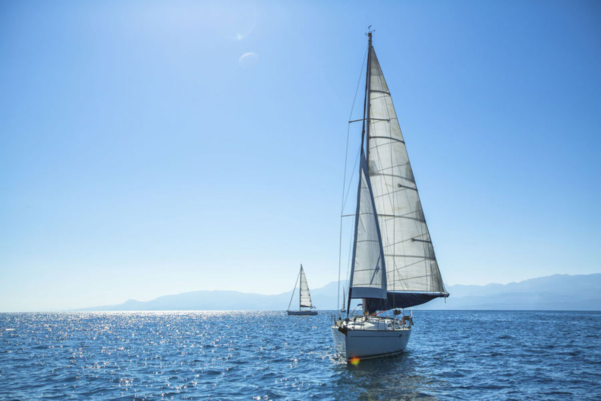 A competitive regatta boat sails on a sunny day