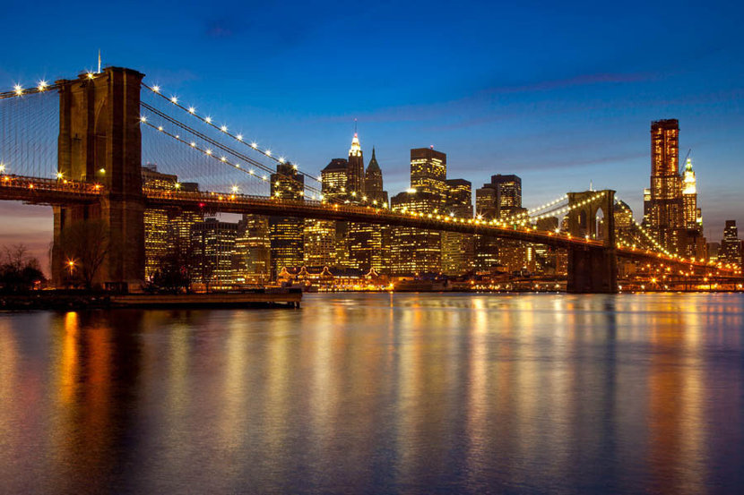 photograph of NYC skyline and the brooklyn bridge at dusk with lights on the bridge and all of new york city