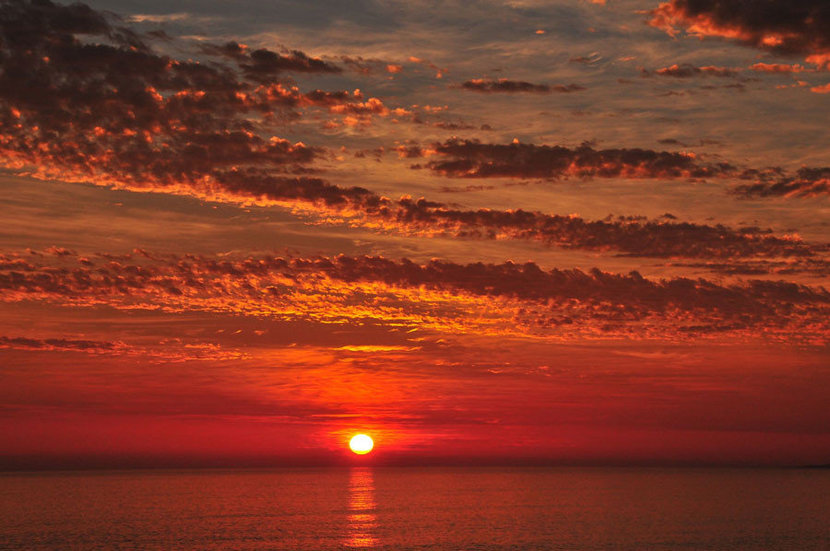 the glowing sun sinks slowly into the ocean creating a vibrant orange glow