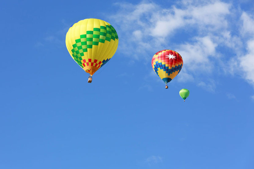 Colorful hot air balloons sail across the sky on a summer day