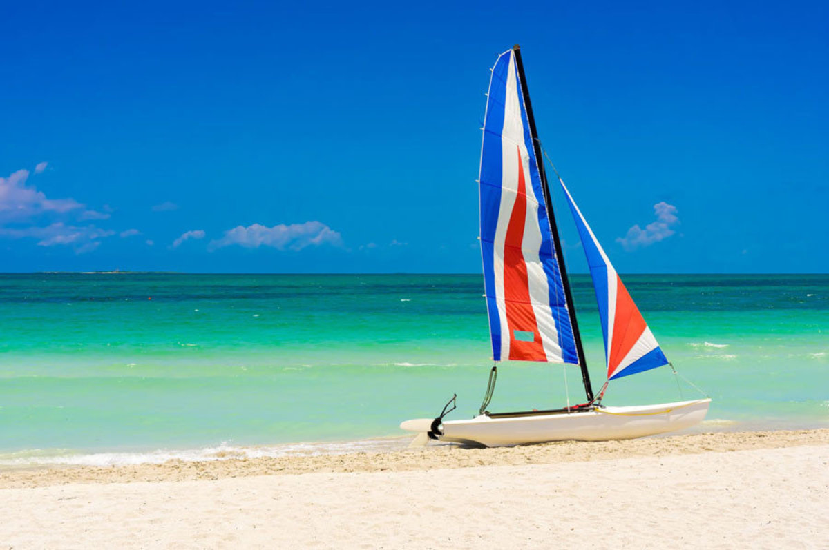 A colorful sailboat rests upon the white sands of a tropical beach