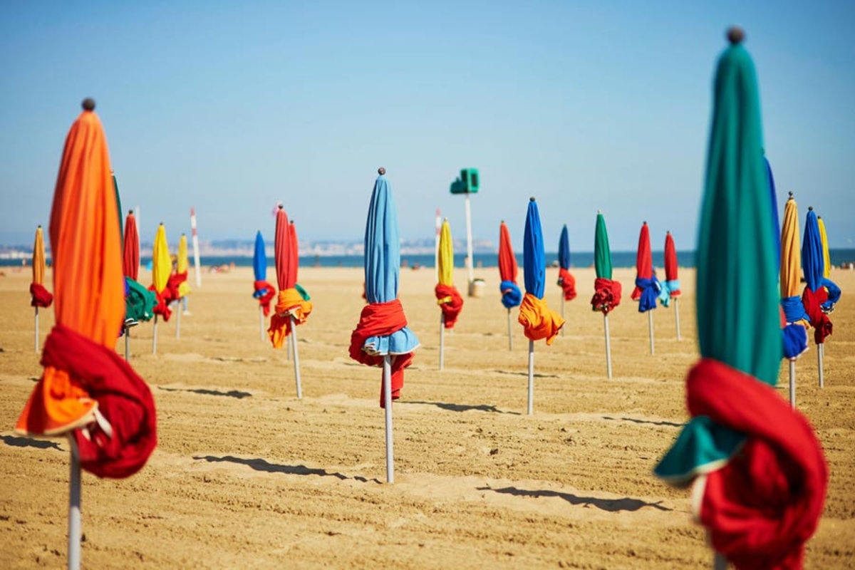 Colorful umbrellas staked into the sand of Deauville, Normandy, France