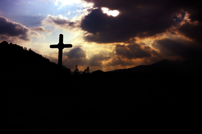 A cross is silhouetted by rays of light that break through an overcast day