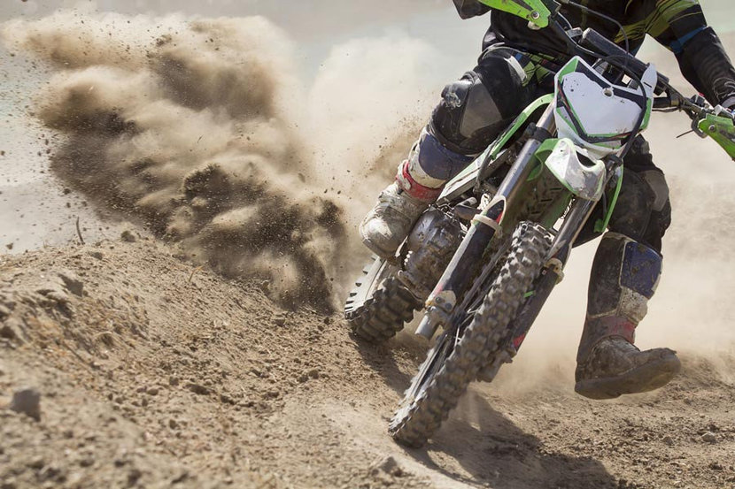 motocross rider kicking up dirt and dust as he speeds off