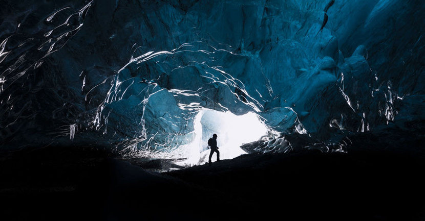 brave hiker is exploring the vast glacial caves in Iceland,