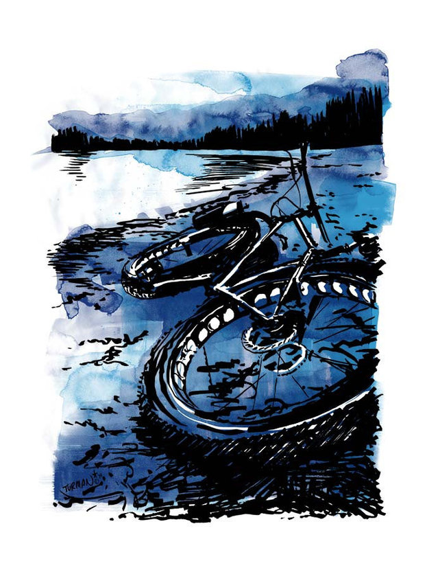 Fat bike lying on the ground near a lakeshore