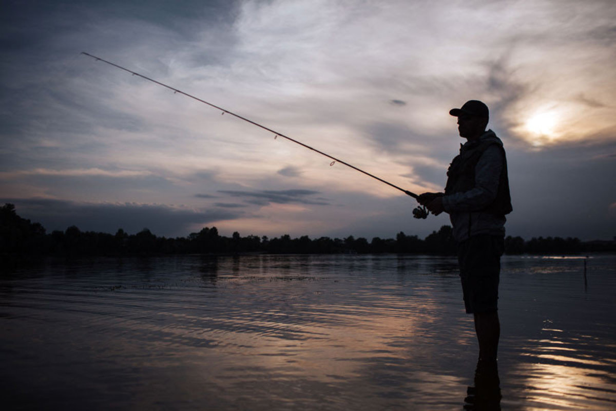 Silhouette of man Fishing In The Dark