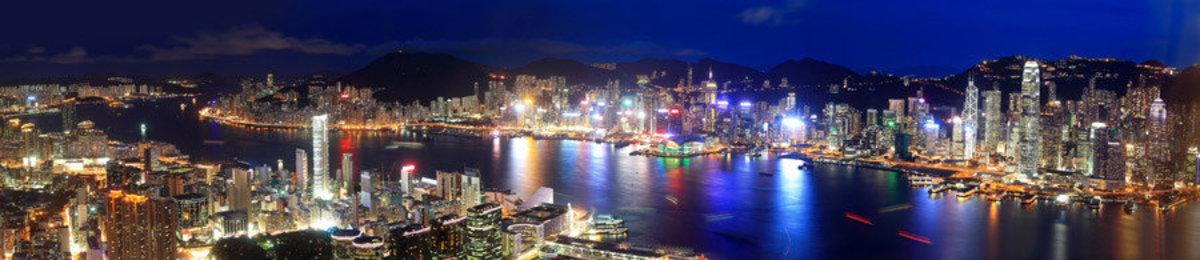 the city of Hong Kong at night in a panoramic format.