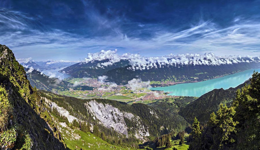 sweeping view of Interlaken shows breathtaking sights such as mountains, a lake, and sky