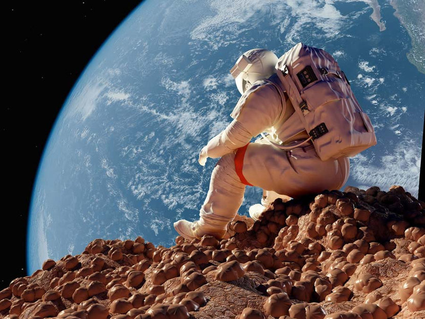 A lone astronaut sits on a deserted planet with Earth in the distance