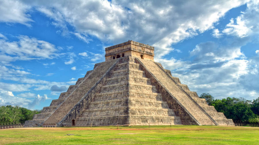 Famous mayan step pyramid of El Castillo stands in grassy field with a cloudy blue sky