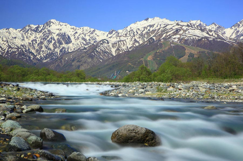 water flowing over rocks with a majestic mountain background in Hakuba Village Japan