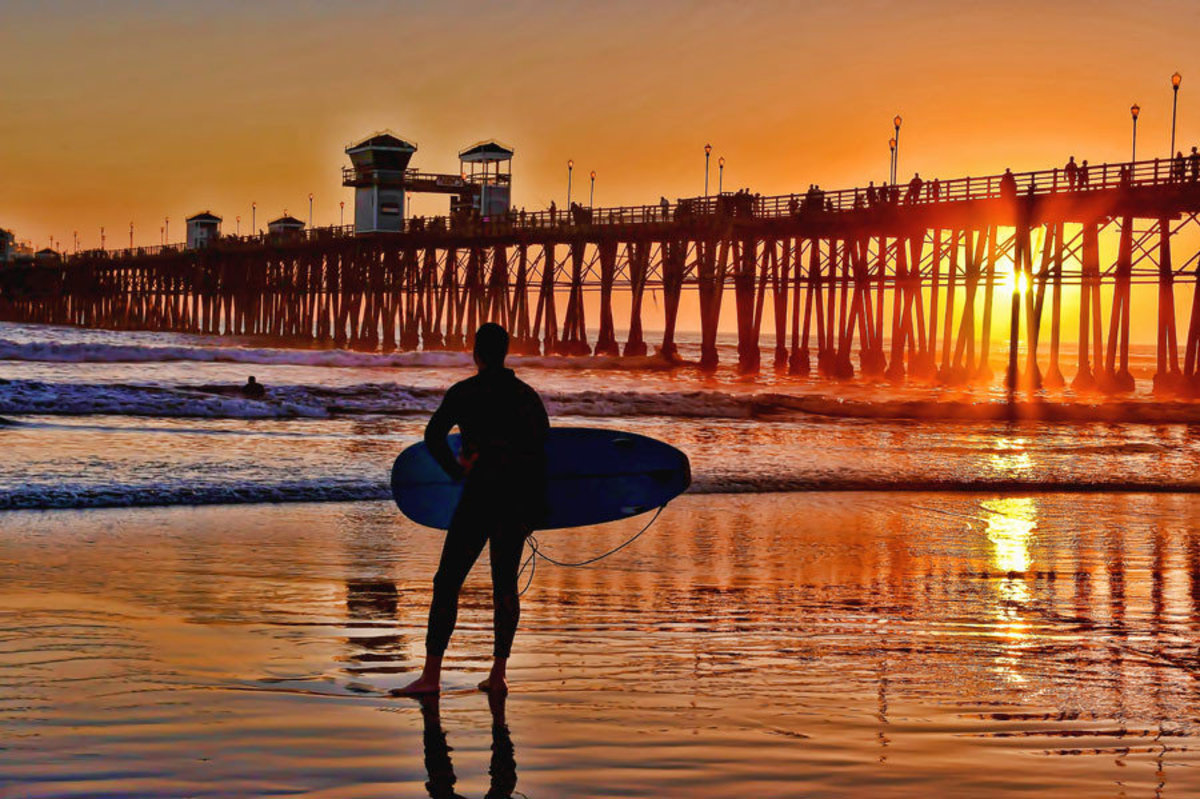 Surfer standing on a beach watching the sunset near Oceanside Pier, California