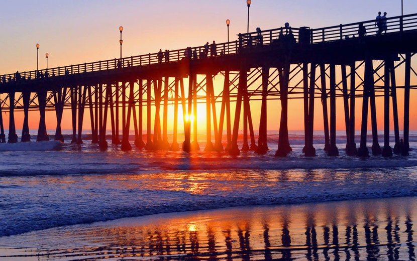 rays of the setting sun shine through the long tall legs of an oceanside pier as waves lap the beach wall mural