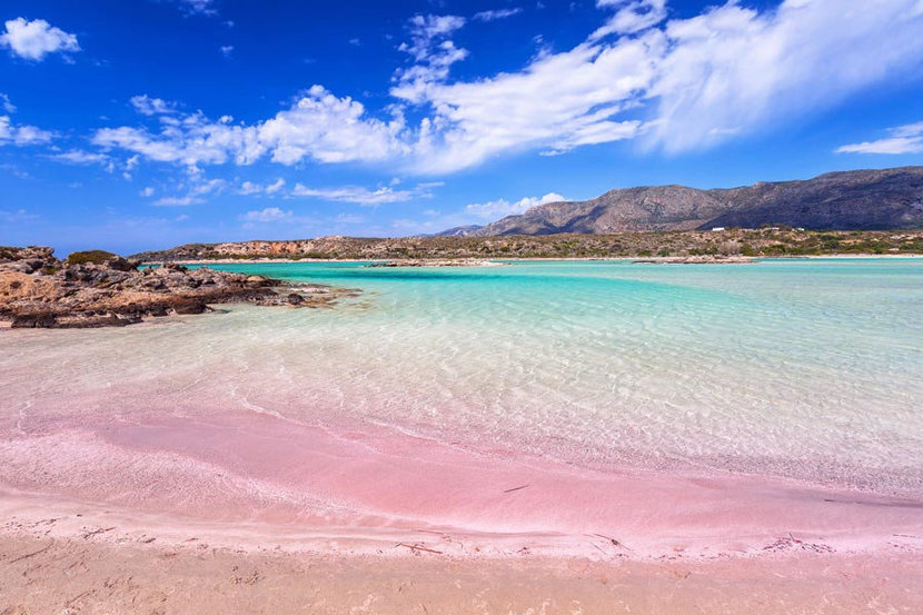 Fluffy white clouds dance above in the blue sky, the luminous waters of the ocean ripple up onto Elofonissi Beach's pink sands