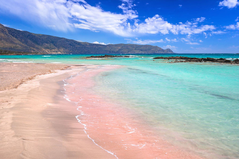 Glistening teal waters of the ocean lap up onto Elafonissi Beach's famous pink-tinged sand