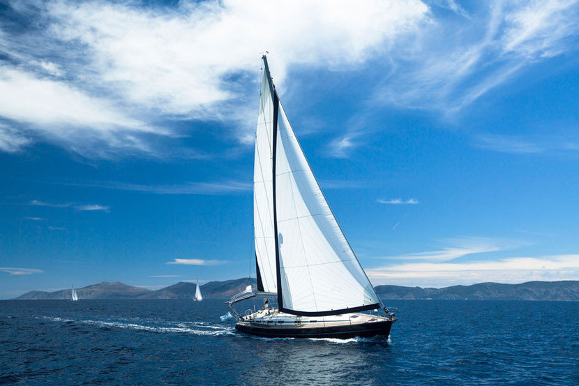 A white sailboat traverses the ocean on a beautiful sunny day