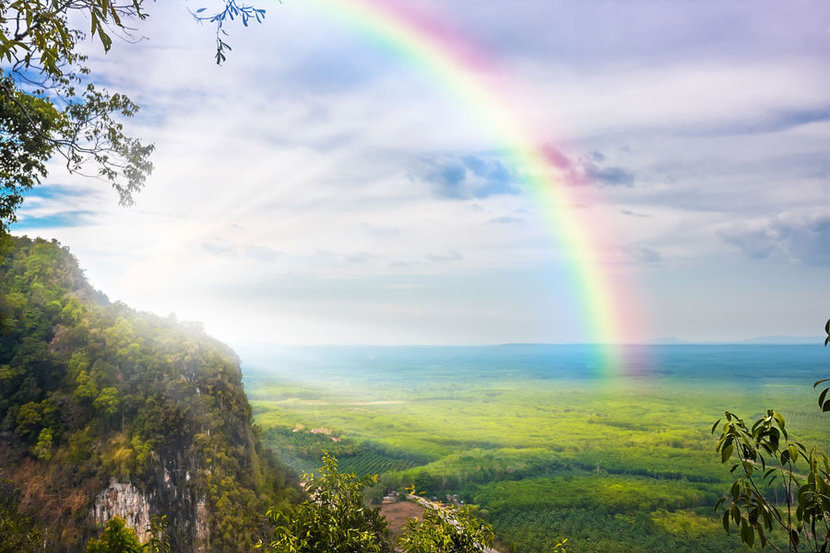 sun shines over the valley while highlighting the beautiful rainbow