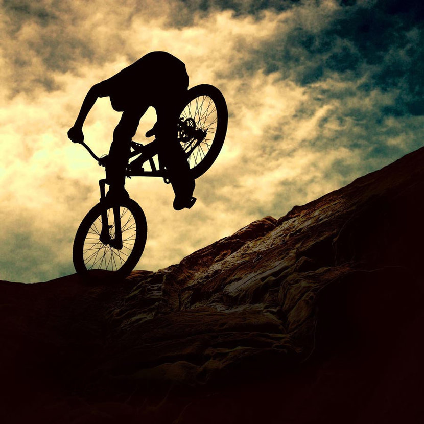 Silhouette of a man on mountain bike at sunset