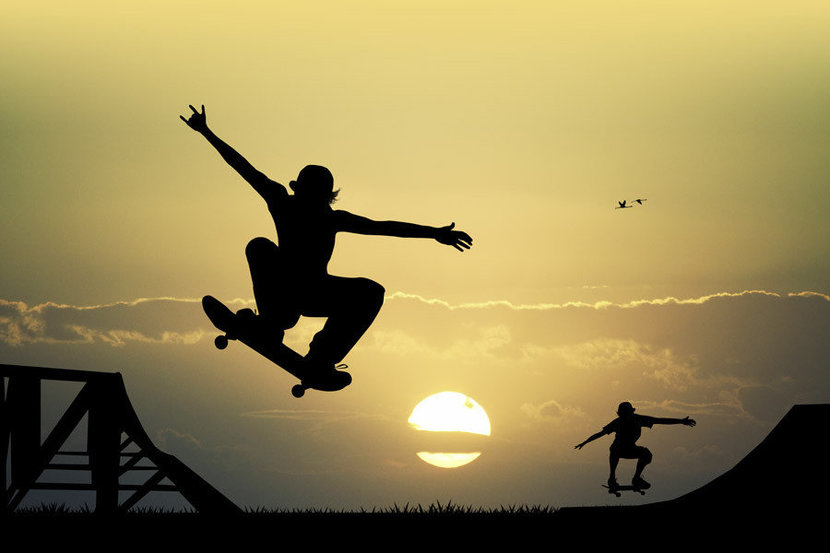 Two skateboarders are silhouetted by the sun