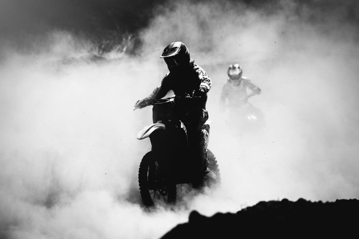 two motorbike racers emerging from kicked up smoke and dirt