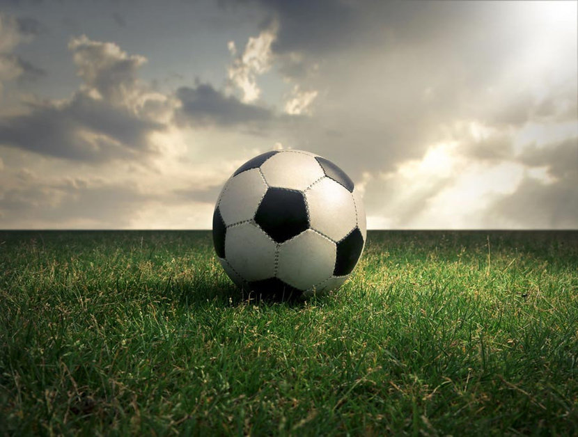sun shines down on a soccer ball in a field