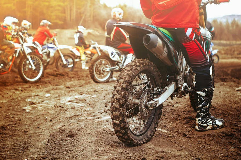 a group of motocross riders gathering at the starting line