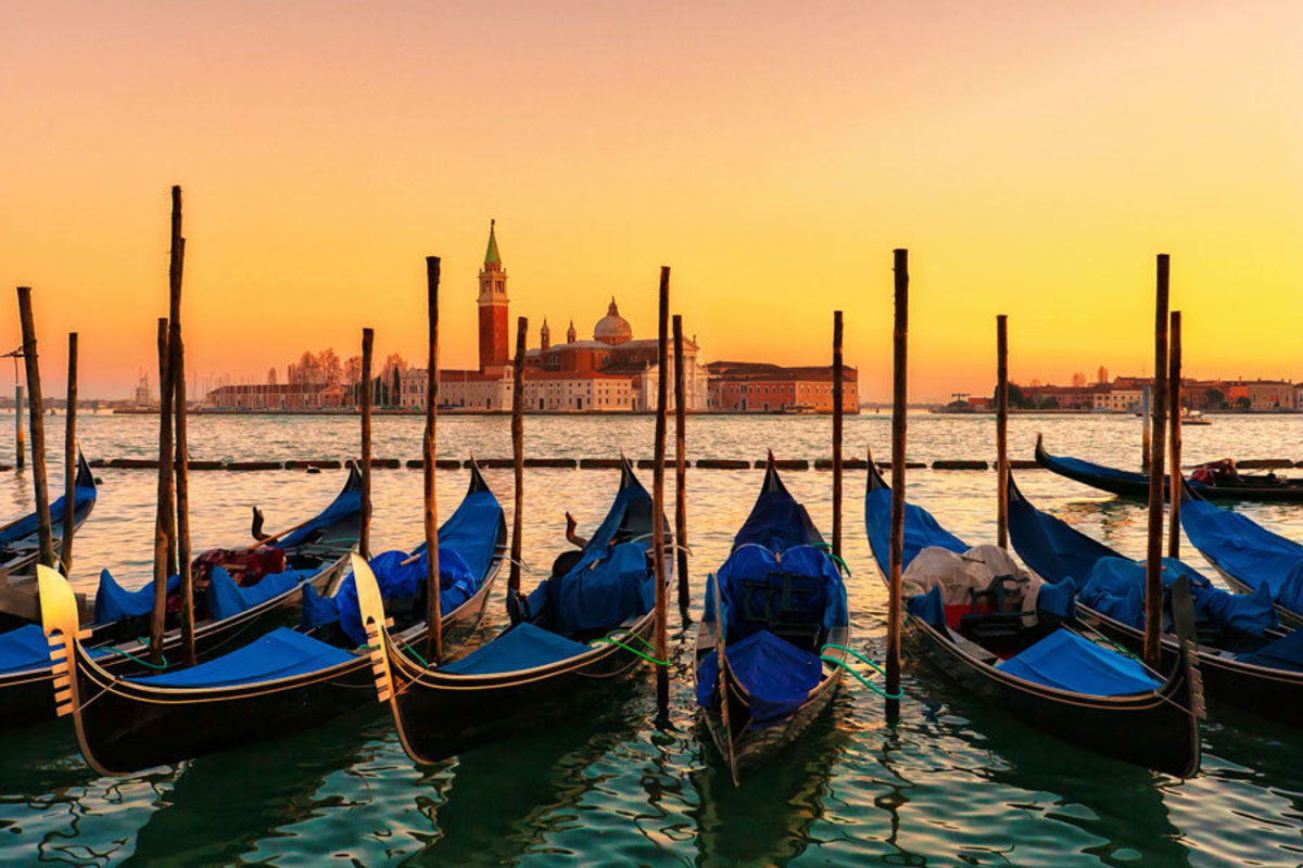 Sunset In Venice wall mural depicts blue gondolas lined up in the water
