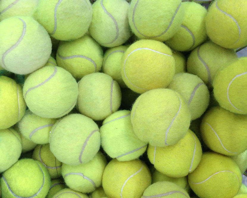 a grouping of tennis balls piled up