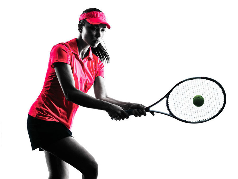 a woman tennis player hitting the ball with a racket
