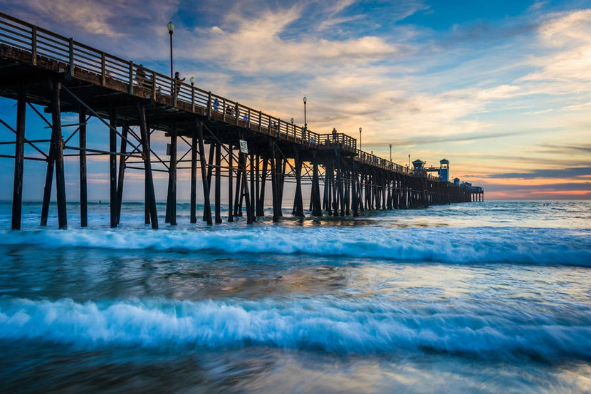 Waves crash upon the shore near a pier in the Pacific Ocean at sunset