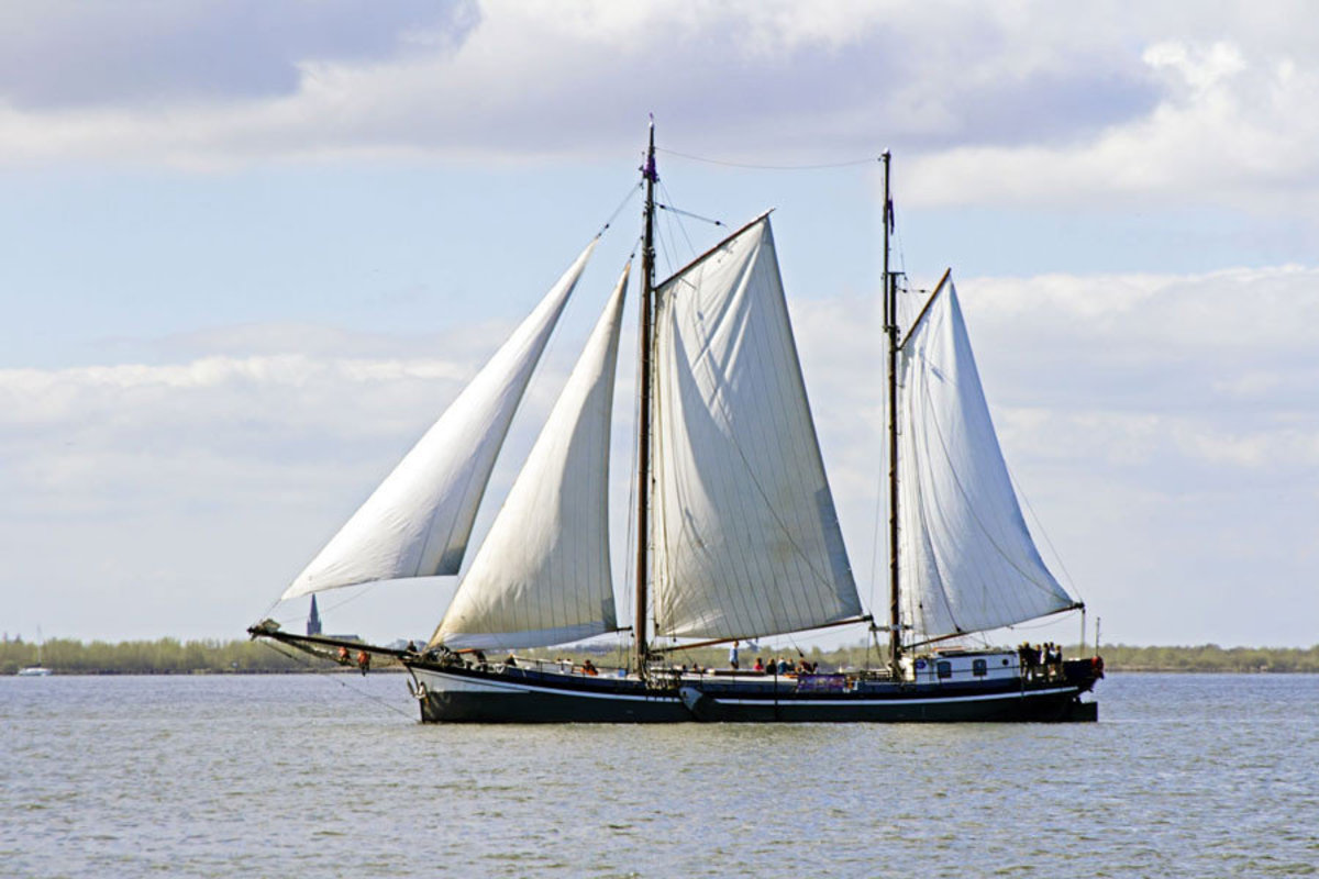A traditional sailing ship coasts along the open water