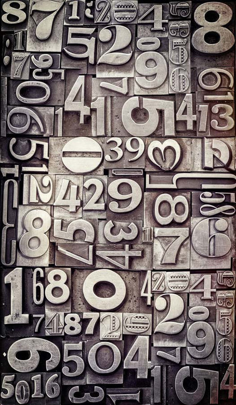 collection of vintage letterpress blocks of different numbers, all of varying fonts