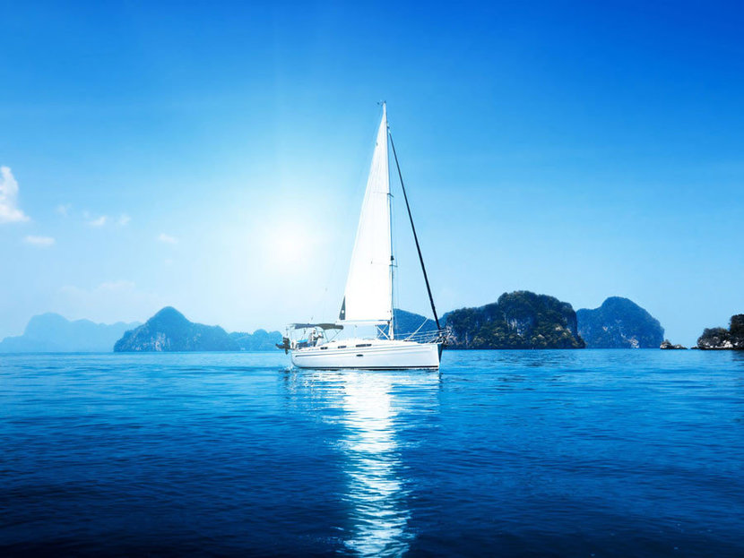 white sailboat sits upon calm ocean waters