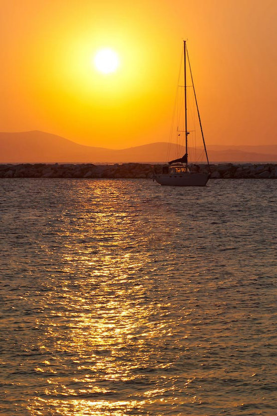 Orange sunset with yacht anchored in in the bay of the calm sea