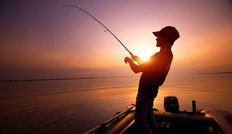 Young Man Fishing At Sunset Wall Mural